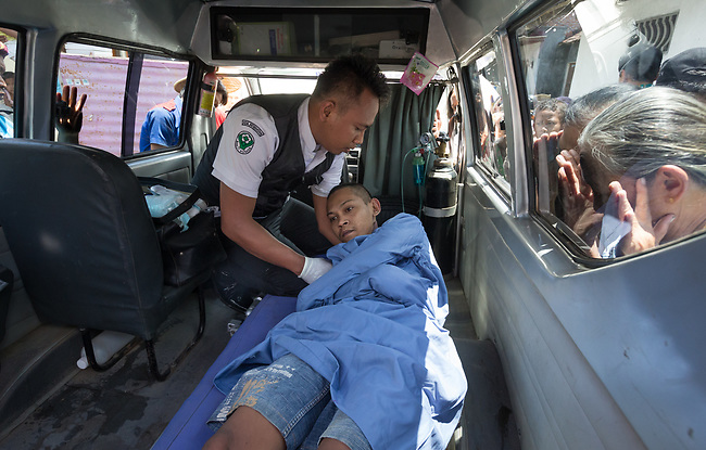 "5 April 2017, Surabaya,East Java,Indonesia: Febrianto, a 24 year old mental illness sufferer is placed in an ambulance in a strait jacket after his release from the chains he has been shackled to a stake for the past two years in a goat shed next to his family in Pehwetan village, East Java. Indonesian Social Affairs Dept. workers cut the bonds and washed his emaciated body and apply first aid before putting him in an ambulance and taking him to a facility in Malang for treatment. Febrianto is a patient in a program called ""E- Shackling"" which aims to free people suffering from mental illness, from the shackles that family often place them in to control them in the wake of a lack of treatment options and which will treat them and enter them in a data base allowing them to be traced before releasing them back to their families. Some people stay chained to a stake or in rooms for years by their families and not all families are willing to take their sick family members back. Picture by Graham Crouch/The Australian"