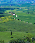 Tuscany, Italy, <br /> winding road among the green rolling hills and fields of Val d'Orcia