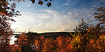 Panoramic fall nature scenery framed with colorful trees at dawn over Smoke lake. Algonquin Provincial Park, Ontario, Canada.