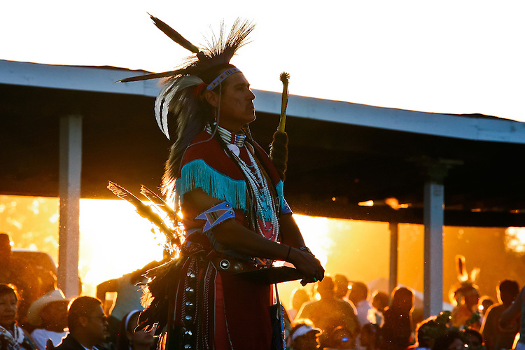 One of the judges watches the dancers as the sun sets behind the dance arbor.