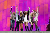 Girlfriends posing for photos in front of the EMP Museum, Northwest Folklife Festival 2016, Seattle Center, Washington, USA.