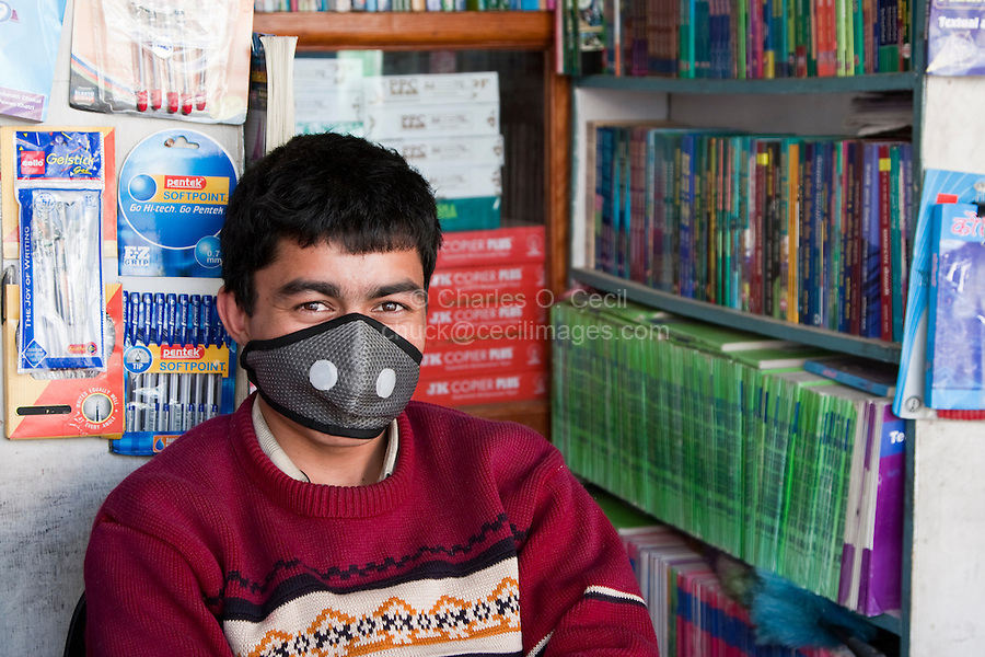 Kathmandu, Nepal.  Nepali Book Store Salesman, Wearing Breathing Mask to Protect Against Air Pollution.