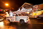 Volcano Telephone's vintage Ford boom truck in Sutter Creek's annual Parade of Lights Christmas parade downtown on a rainy night in the  Mother Lode of Calif.