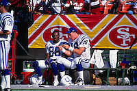 SAN FRANCISCO, CA - Peyton Manning of the Indianapolis Colts talks to teammate Marvin Harrison on the bench during a game against the San Francisco 49ers at Candlestick Park in San Francisco, California on October 18, 1998. (Photo by Brad Mangin)