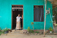 EM Podimaneke, 49, stands outside her home where an elephant killed her husband in June 2013. Human-elephant conflict has increased as the animals habitat becomes smaller due to deforestation and habitat fragmentation. It is estimated that around 50 people are killed by elephants each year in the country, while over 100 elephants are also killed as farmers try to protect their land.