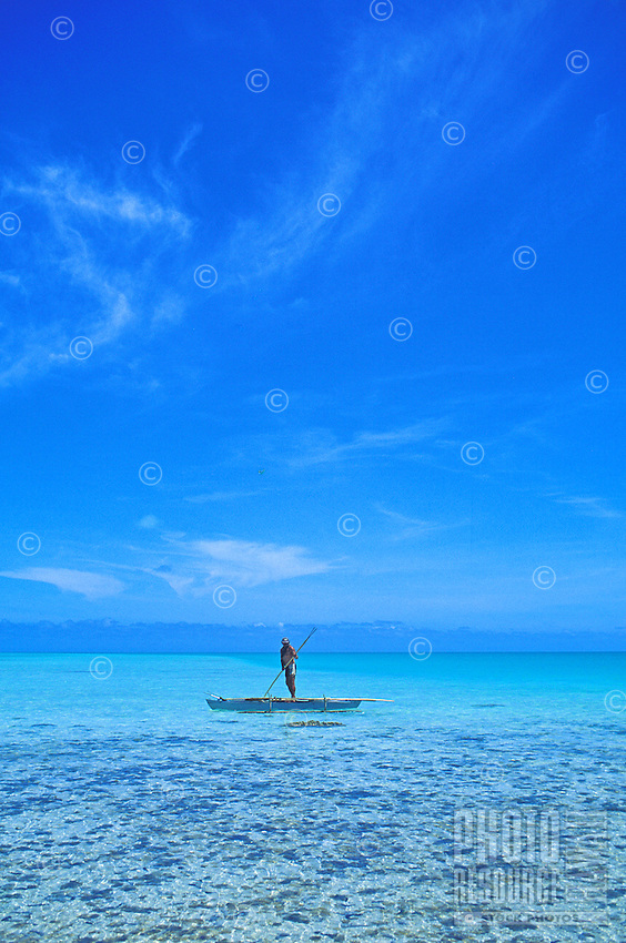 Fisherman is framed by blue in the Aitutaki Lagoon, Aitutaki, Cook Islands