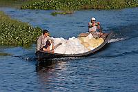 Myanmar, Burma.  Two Men in Canoe Transporting Bags of Rice, Inle Lake, Shan State.