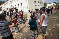 Zentrale Auslaenderbehoerde und BAMF-Aussenstelle in Eisenhuettenstadt.<br /> Bundesinnenminister Thomas de Maiziere und brandeburgs Ministerpraesident Dietmar Woidke besuchten am Donnerstag den 13. August 2015 die Zentrale Auslaenderbehoerde und BAMF-Aussenstelle in Eisenhuettenstadt. Sie liessen sich von Mitarbeitern die Situation in der Einrichtung zeigen und erklaeren, sprachen mit Fluechtlingen und besichtigten das auf dem Gelaende befindliche Abschiebegefaengnis.<br /> Der Besuch des Bundesinnenministers und des Ministerpraesidenten wurde von etwa 40 Journalisten begleitet.<br /> Im Bild: Fluechtlinge vom Balkan betrachten Ministerpraesident Woidke, Bundesinnenminister de Maiziere und den Pressetross bei ihrem Rundgang.<br /> 13.8.2015, Eisenhuettenstadt/Brandenburg<br /> Copyright: Christian-Ditsch.de<br /> [Inhaltsveraendernde Manipulation des Fotos nur nach ausdruecklicher Genehmigung des Fotografen. Vereinbarungen ueber Abtretung von Persoenlichkeitsrechten/Model Release der abgebildeten Person/Personen liegen nicht vor. NO MODEL RELEASE! Nur fuer Redaktionelle Zwecke. Don't publish without copyright Christian-Ditsch.de, Veroeffentlichung nur mit Fotografennennung, sowie gegen Honorar, MwSt. und Beleg. Konto: I N G - D i B a, IBAN DE58500105175400192269, BIC INGDDEFFXXX, Kontakt: post@christian-ditsch.de<br /> Bei der Bearbeitung der Dateiinformationen darf die Urheberkennzeichnung in den EXIF- und  IPTC-Daten nicht entfernt werden, diese sind in digitalen Medien nach §95c UrhG rechtlich geschuetzt. Der Urhebervermerk wird gemaess §13 UrhG verlangt.]