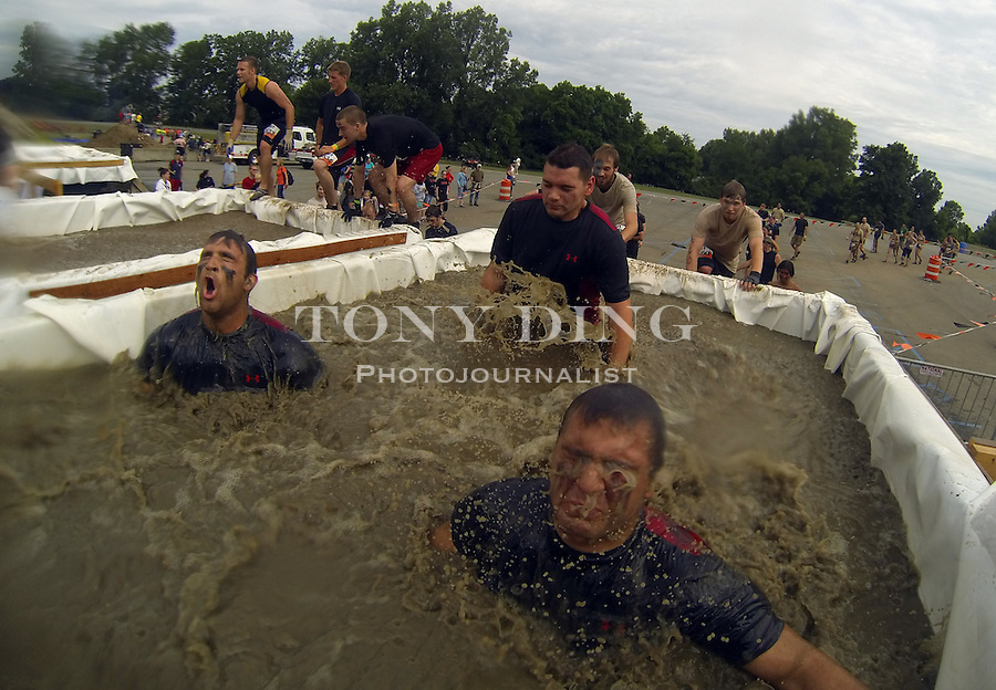 """16 April 2010: Competitors jump into a deep ice water tub called the """"Arctic Enema"""" and have to dive under a bar in one of twenty obstacles in the Tough Mudder adventure endurance race at Michigan International Speedway in Brooklyn, Michigan."""