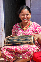 Bhaktapur, Nepal.  Woman Playing a Drum while Sitting with Friends on her Front Porch.