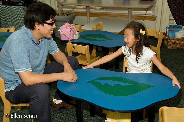 MR / College Park, Maryland.Center for Young Children, laboratory school within the College of Education at the University of Maryland. Full day developmental program of early childhood education for children of faculty, staff, and students at the university..Father and daughter (5, Korean-American) talk together at a table in multi-use common area..MR: Jeo1 Jeo2.© Ellen B. Senisi