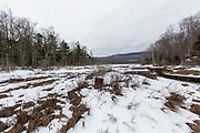 The backside of Elbow Pond in Woodstock, New Hampshire on a cloudy winter day. The Elbow Pond Branch of the Gordon Pond Railroad (1905-1916) traveled through this area (just beyond the 55 gallon drum right to left).