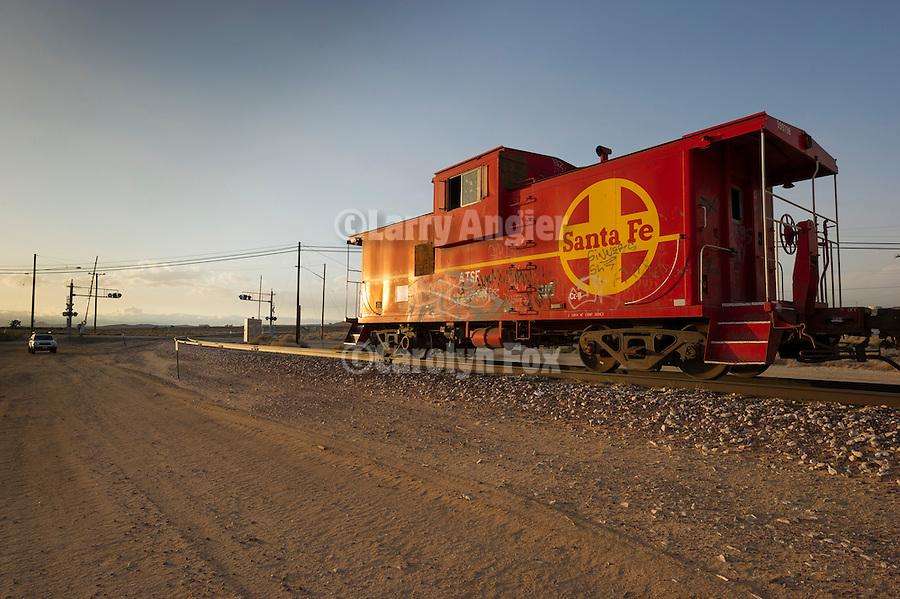 Santa Fe railroad caboose at the end of a line of mineral hopper cars, Boron, Calif.