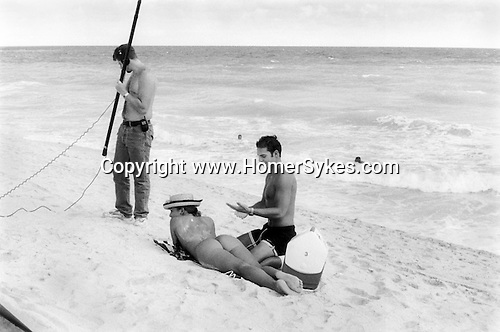 South Beach, Miami, Florida 1999. An impromptu film set, they have filming a Spanish speaking mid afternoon love story. The man is rubbing sun oil onto the woman's. back. He's concerned that he has mixed sand with the oil. A sound engineer holds the boom. Two swimmers try and make the scene look real. 1990s USA.