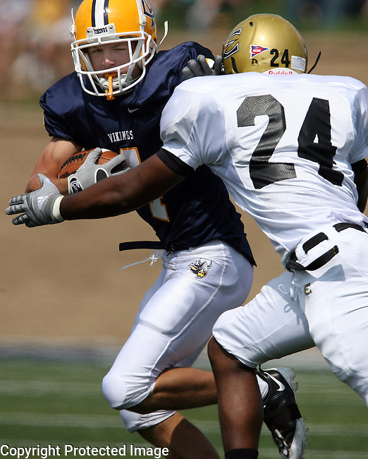 SIOUX FALLS, SD - SEPTEMBER 5: Sam Holsen #4 of Augustana looks for running room past Travon Brooks #24 of Emporia State University in the first quarter Saturday afternoon at the Kirkeby-Over Stadium on the Augustana College campus. (Photo by Dave Eggen/Inertia)