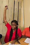 Education high school classroom scenes female student raising hand in class