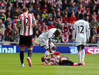 Pictured: Dwight Tiendalli of Swansea (CENTRE TOP) helps Fabio Borini of Sunderland from the ground after he fouled him. Sunday 11 May 2014<br /> Re: Barclay's Premier League, Sunderland v Swansea City FC at the Stadium of Light, Sunderland, UK.