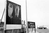 """Jordan. Aqaba. An old Mercedes car is parked on the road. A sign with arabic writings. Portraits of King Abdullah II and his father King Hussein, both dressed as arab bedouins. His Majesty King Abdullah II bin Al Hussein, is the actual King of The Hashemite Kingdom of Jordan.His Majesty King Abdullah II bin Al Hussein is the 43rd generation direct descendant of the Prophet Muhammad. He assumed his constitutional powers as Monarch of the Hashemite Kingdom of Jordan on February 7th, 1999, the day of the death of his father, the late Royal Highness King Hussein bin Talal (1935-1999), known to his  people as Al-Malik Al-Insan (""""The Humane King"""").  © 2002 Didier Ruef"""