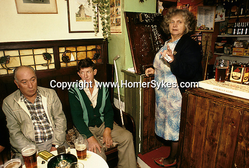 High Ham, Somerset. 1980's<br /> At the Kings Head Inn, landlady Louisa May Brown known as Maisie is scoring the darts match in chalk on the underside of the wooden flap leading into the bar. Two locals enjoy a quite pint and ciggy and wait for their turn.