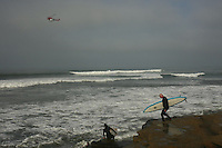 A San Diego Fire Department helicopter with a Lifeguard onboard moves slowly over the surf line-up off Sunset Cliffs in Ocean Beach San Diego California as surfers prepare to enter the water on Wednesday, December 5, 2007.  A large storm pushing towards the coast brought 10ft high waves to the area.