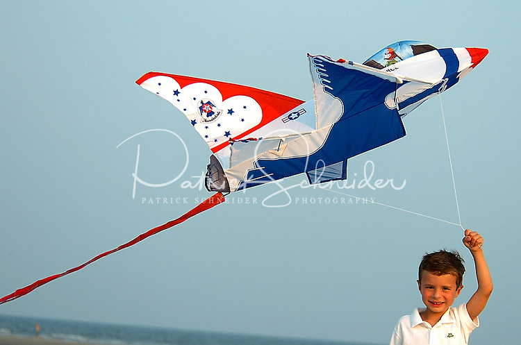 A young boy flies an airplane-shaped kite on the windy ocean beach on Sullivan's Island, SC.
