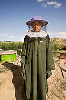 A beekeeper dressed in protective clothing stands beside his hives.