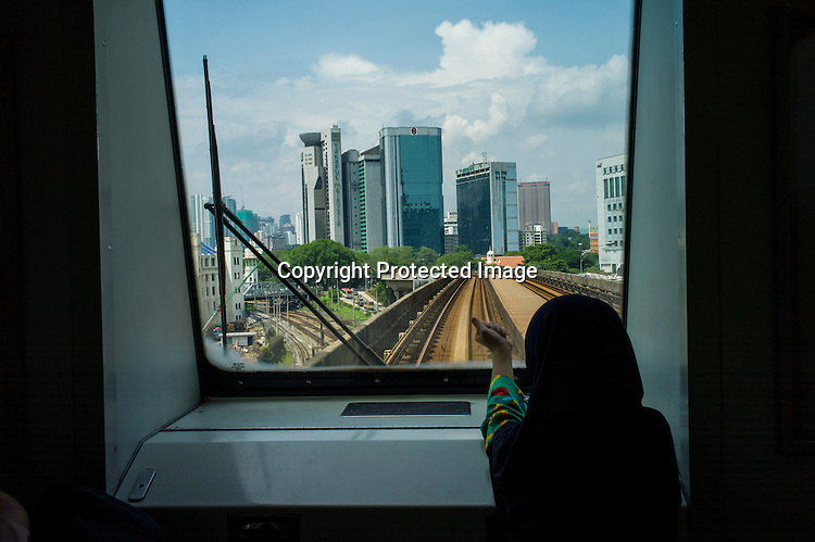 A young girl looks out of the window of a train with Kuala Lumpur skyline in front of her in Kuala Lumpur, Malaysia. Photo: Sanjit Das/Panos