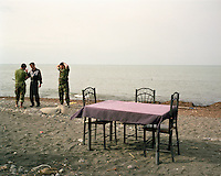 Two guards listen to a local man at a beach cafe in Lankaran, overlooking the Caspian Sea.