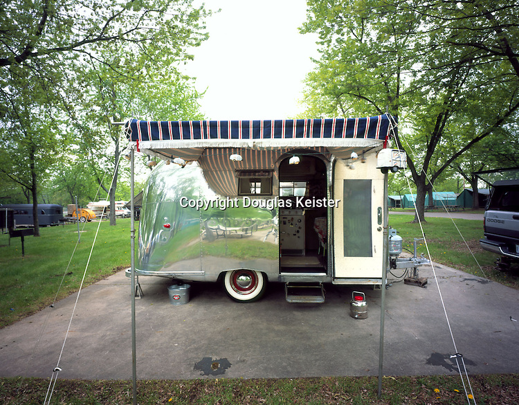 """1960 Pacer. At sixteen and one-half feet and weighing 2500 pounds, the Pacer was the most diminutive trailer that Airstream manufactured in 1958, 1959 and 1960. In 1961, the Bambi replaced the Pacer. All of these modestly scaled trailers are highly desirable among collectors. The owners of this Pacer, which they call, """"the Silver Twinkee"""", spent a lot of time and elbow grease restoring their vintage trailer. During the polishing phase of their restoration they wore out two electric buffers while applying three jars of """"Mother's"""" polish. Dexter and Alicia Leonard's Pacer photographed at Camp Dearborn, Michigan"""