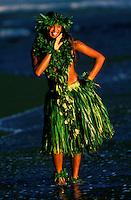 Local Hawaiian young woman dancing in Waipio Valley wearing ti leaves skirt maile lea