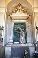 Picture and image of the stone sculpture of a  mourning widow who is bringing a crown and knocking on a sepulcher's bronze door, which holds the bas relief of an hourglass, a classic symbol of the passing of time. This theme of the sorrowful survivor in front of the sepulcher's door comes from the Monument dedicated to Maria Christina, Duchess of Teschen, Maria Theresa of Austria's daughter, a neoclassical sculpture. In this version the widow is wearing fashionable clothes, which have been accurately represented, and her openwork shawl. Sculptor G. B. Cevasco 1875. The monumental tombs of the Staglieno Monumental Cemetery, Genoa, Italy