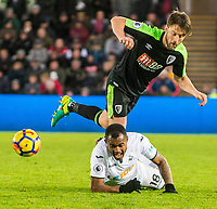 A Bournemouth player falls over Jordan Ayew of Swansea City during the Premier League match between Swansea City and Bournemouth at The Liberty Stadium, Swansea, Wales, UK. Saturday 25 November 2017