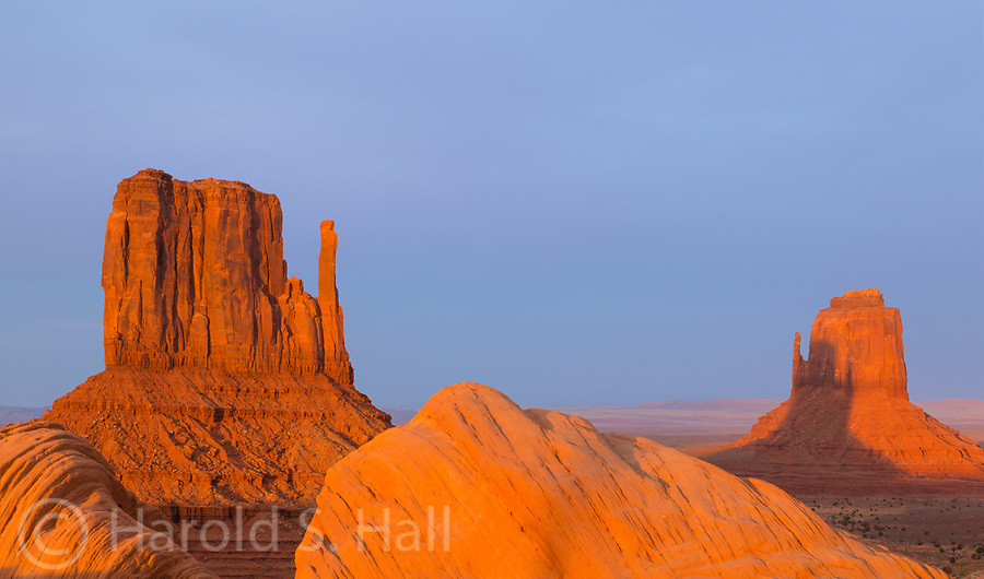 The sun sets on Monument Valley Utah causing the shadow of the East Mitten to be cast on the West Mitten.  These buttes are called mittens due to their shape.