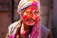 Portrait of Hindu man with his face, turban, and clothes covered in color powder during the Holi celebrations in Mathura, Uttar Pradesh, India