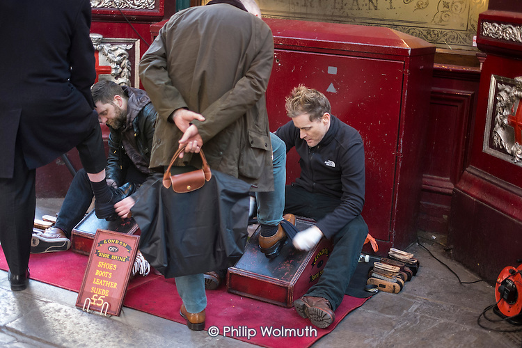 Two men shining shoes in Leadenhall Market, close to the Lloyds Bulding and other major City of London financial institutions.