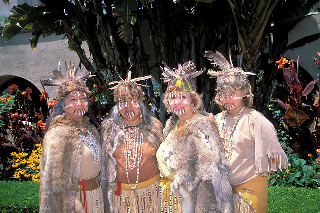 A group of four Mission Indian women, Costanoan Rumsen Ohlone, dressed in traditional rabbit skin capes, grass skirts, shell beads and feather headdresses at the Museum of Man in Balboa Park San Diego CA