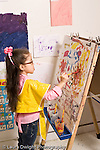 Education preschool 4 year olds art activity girl in smock painting at easel recognizable figure human being vertical