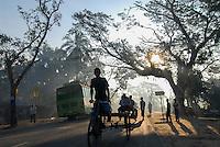BANGLADESH, Khulna District, morning mist at road in village, Bus and bicycle rikshaw / BANGLADESCH Khulna , Menschen, Rikscha und Bus im Morgennebel auf einer Strasse in einem Dorf