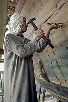 Kuwait April 1967.  Carpenter Hammering Nails into Hull of Dhow.