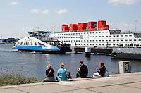 Nederland Amsterdam  2015 06 10 . Het Amstel Botel en de pont bij het NDSM Terrein. Het botel is een drijvend hotel. In de rode letters kan ook geslapen worden