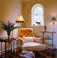 A tree has been painted on the wall in this corner of the living room behind a faded and polished leather armchair