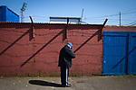 A home fan pauses outside the turnstiles outside Palmerston Park, Dumfries before Queen of the South hosted Dundee United in a Scottish Championship fixture. The home has played at the same ground since its formation in 1919. Queens won the match 3-0 watched by a crowd of 1,531 spectators.