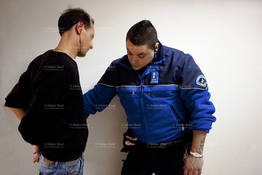 """Switzerland. Geneva. BSR (Brigade de sécurité routière) police station. A police officer and a handcuffed french man, who was arrested because he was driving under the influence of alcohol. He is bleeding blood from his right ear. Driving under the influence (DUI), drunken driving, drunk driving, drink driving, operating under the influence, drinking and driving, or impaired driving is the act of driving a motor vehicle with blood levels of alcohol in excess of a legal limit (""""Blood Alcohol Content"""", or """"BAC""""). A police station or station house is a building which serves police officers and contains offices, temporary holding cells and interview/interrogation rooms. The BSR police station is located in the Grand-Lancy area. 01.04.12 © 2012 Didier Ruef"""