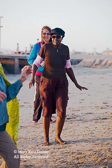 African American female senior dances and exercises in senior exercise class on Playa Del Rey Beach in Los Angeles, California