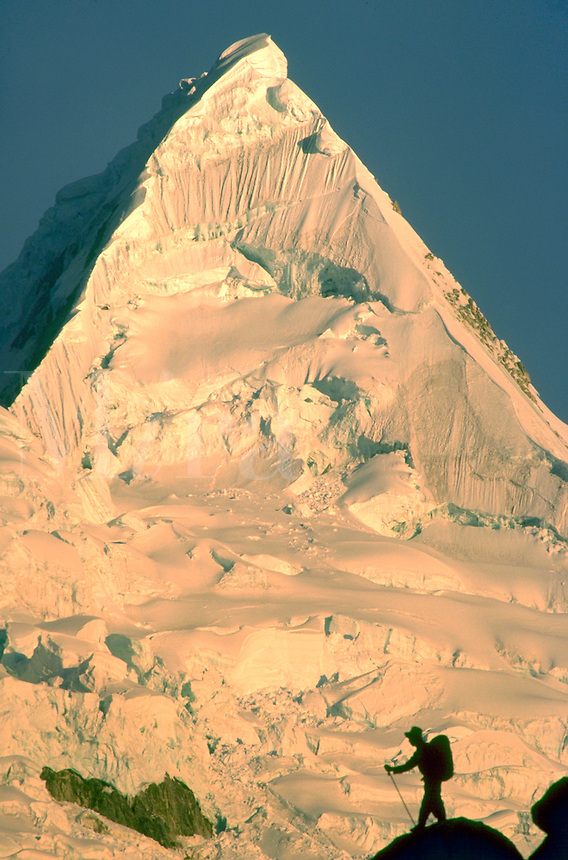 """A climber silhouetted against the rocky face of """"""""The World Most Beautiful Peak"""""""", Cordillera Blanca in Peru."""