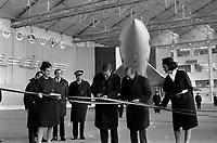 Ateliers Sud Aviation (Saint-Martin-du-Touch). 11 décembre 1967. Vue d'ensemble de face de Jean Chamant (ministre des Transports) à droite et de Anthony Neil Wedgwood Benn (ministre anglais de la Technologie) coupant le ruban officiel, sont entourés de deux hôtesses ; en arrière-plan prototype du Concorde (vue de face). Cliché pris lors de la présentation officielle du prototype français du Concorde.