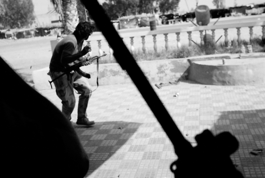 Rebel fighter reacts to incoming fire from Gaddafi soldiers at the strategical crossroads to Tripoli and Zawiya near Bir Ayad, Libya.