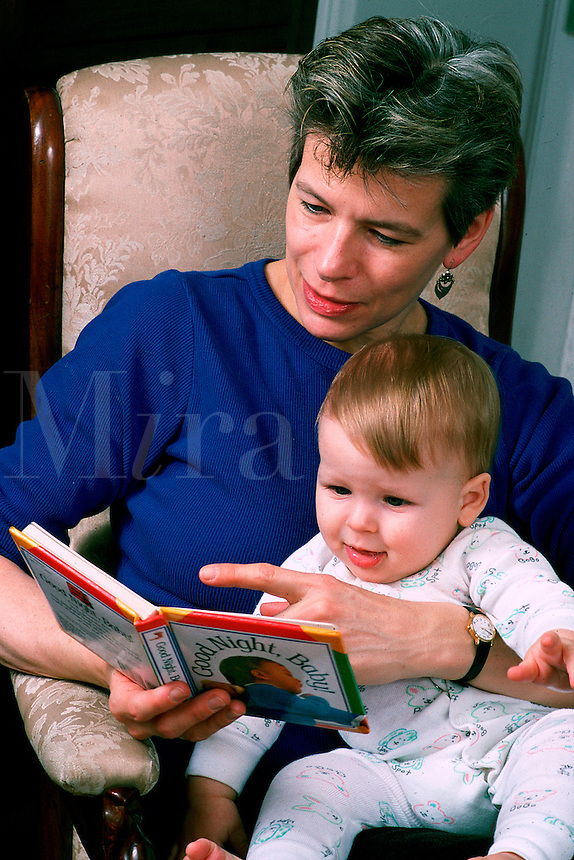 Mother reads to her toddler son.