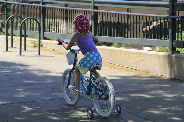 Young girl riding her bike with training wheels on a sidewalk in Denver, Colorado. .  John offers private photo tours in Denver, Boulder and throughout Colorado. Year-round.
