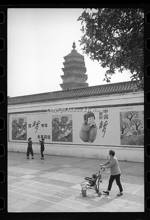 """Lu'an, Anhui province, China - Elderly women practice ballroom dance in front of the """"China Dream"""" propaganda billboards against a backdrop of the Northern Pagoda, May 2017."""